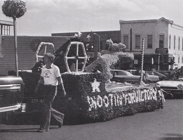 "The Senior float, passing by Guisinger's Music shop on the Fayetteville square, shows a bulldog being catapulted out of a cannon toward a goal post with the theme: ""Shootin' for a Victory."""