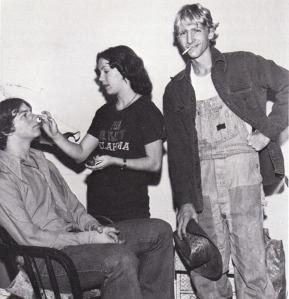 Vickie Hileman applies Sean Harison's make-up while finished product Mike Smith puffs on a cigarette.