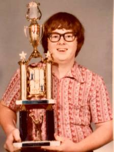 Photo of Stephen McGinnis holding a music competition trophy.